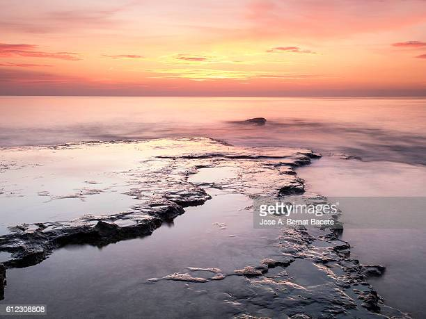 Lights of the Sun to the dawn opposite to the sea on the coast, with rocks and water puddles