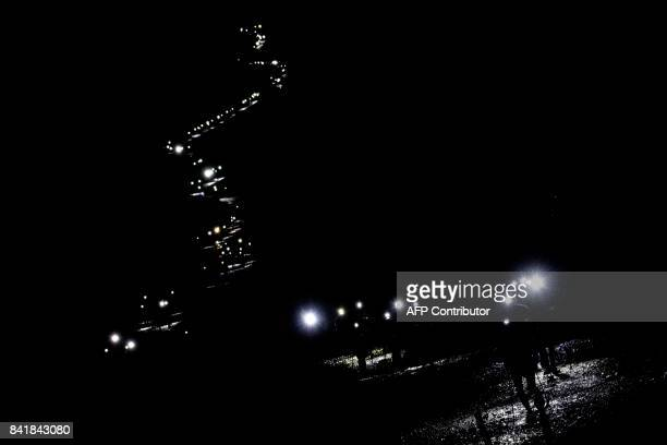 TOPSHOT Lights of ultratrailers competing illuminate the way on September 1 2017 in Les Contamines Montjoie during the 15th edition of the Mount...