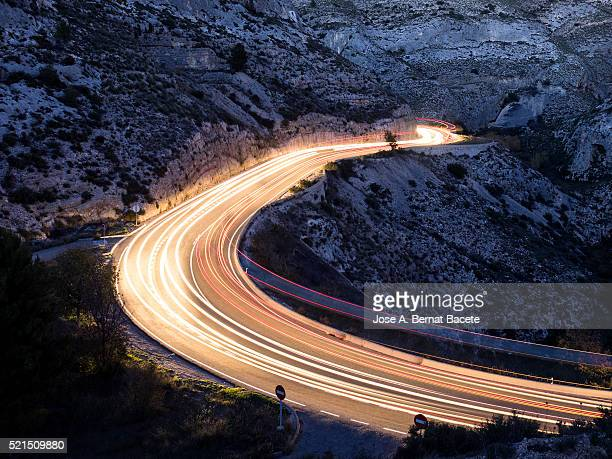 Lights of vehicles circulating along a road between mountains and ravines to the dusk