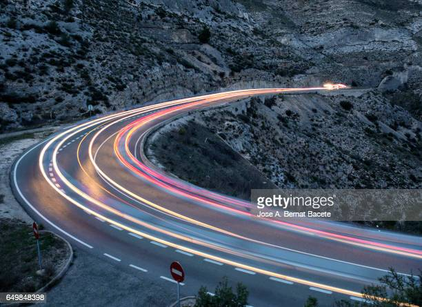 lights of vehicles circulating along a road of mountain with curves closed in the night - hairpin curve stock photos and pictures