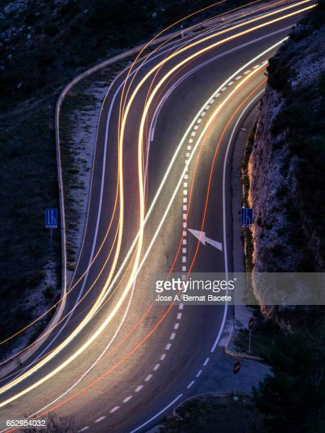 Lights of vehicles circulating along a road of mountain with curves closed In the shape of s,  in the night