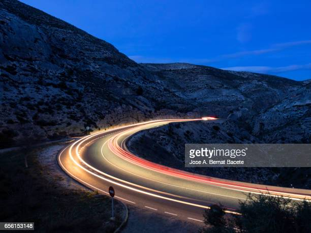 Lights of vehicles circulating along a road of mountain with curves closed in the night