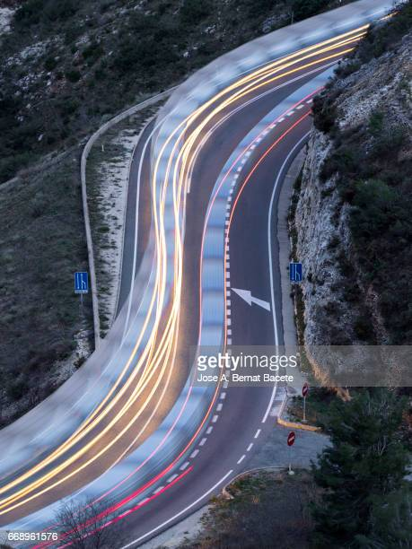 lights of vehicles circulating along a road of mountain with curves closed in the shape of s,  in the night - tipo de transporte stock pictures, royalty-free photos & images