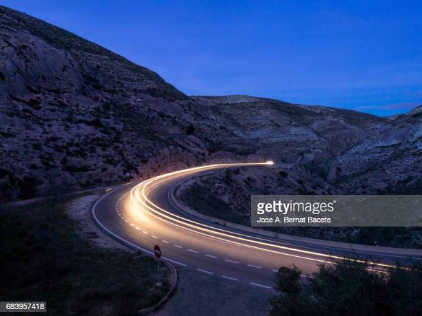 lights of vehicles circulating along a road of mountain with curves closed in the night - cañón tipo de valle fotografías e imágenes de stock