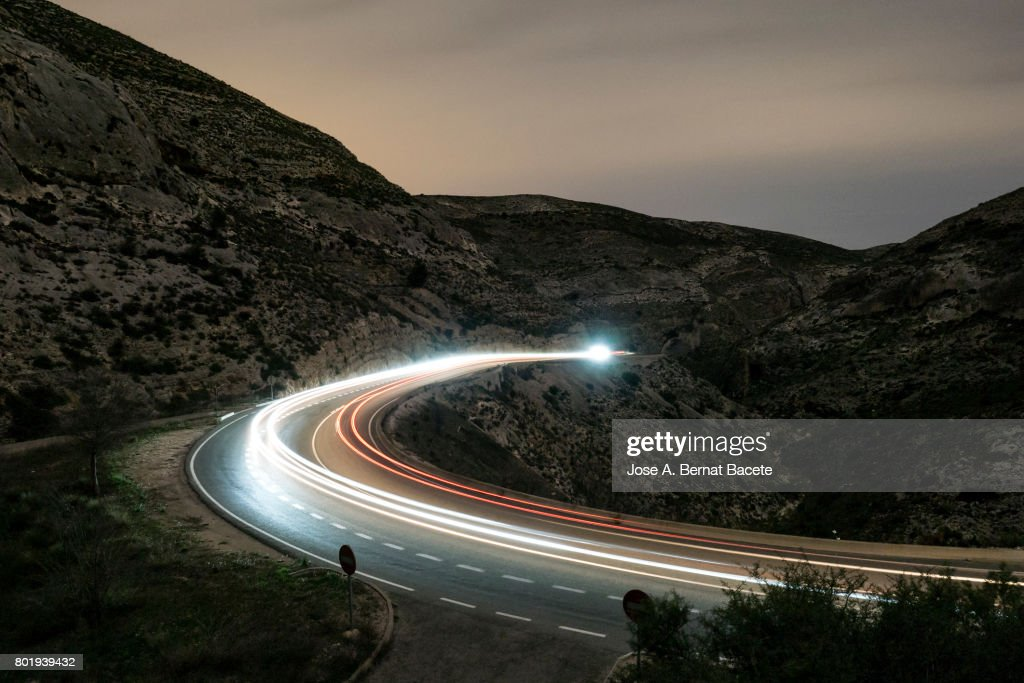 Lights of vehicles circulating along a road of mountain with curves closed in the night : Stock Photo