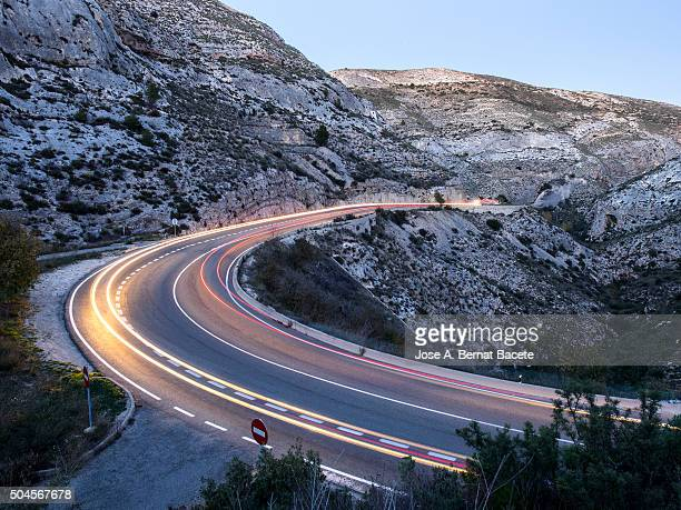 Lights of vehicles circulating along a road with curves to the dusk