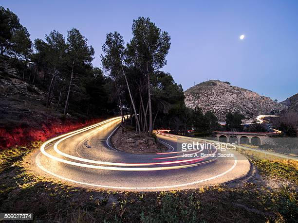 Lights of vehicles in movement circulating along a carretera with curves very closed in the moonlight.