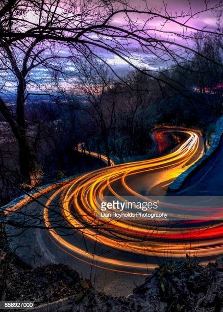 lights of vehicles on mountain road at night - global village stock pictures, royalty-free photos & images