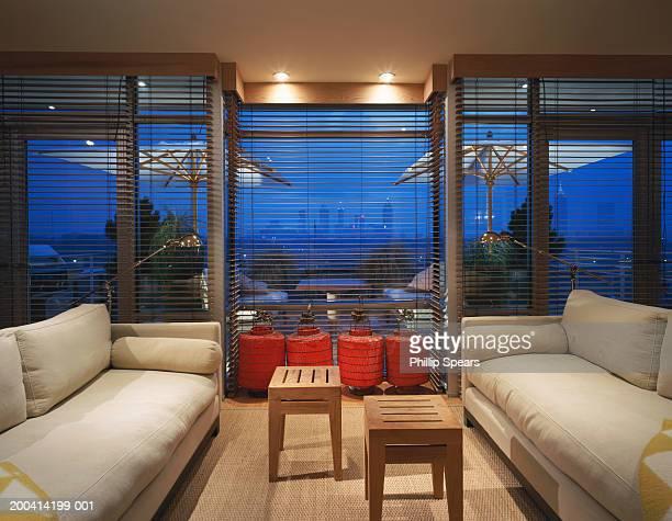 Lights on in living room, view of city skyline through window, night