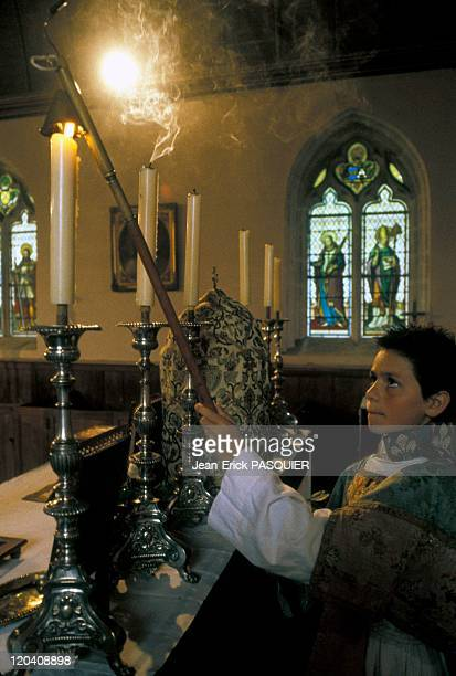 Lights Out In France In 1987 An altar boy is careful to extinguish all the candles of the church after High Mass on Sundaya Country Priest Father...