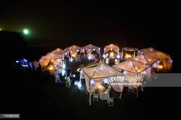 Lights shine at a beachside wedding at nights