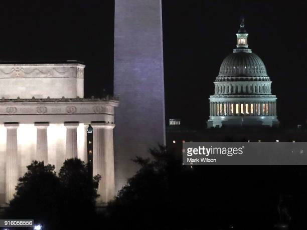 Lights shine at The US Capitol along with the Washington Monument and Lincoln Memorial in the early hours of Friday morning on February 9 2018 in...