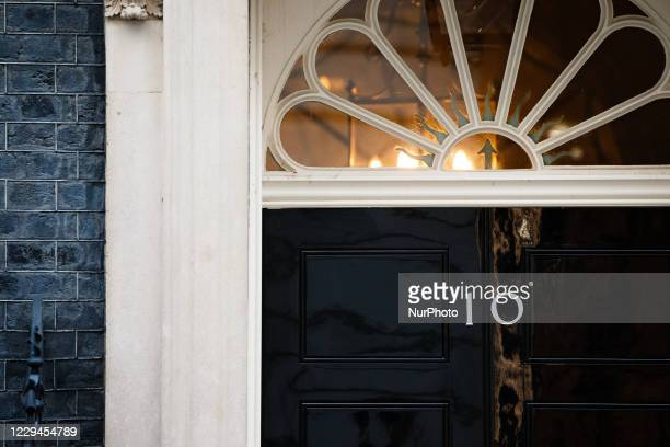 Lights shine behind the door of 10 Downing Street in London, England, on November 4, 2020.
