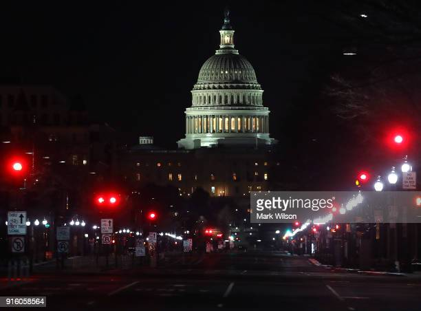 Lights shine down Pennsylvania Avenue leading to the US Capitol in the early hours of Friday morning on February 9 2018 in Washington DC Despite an...