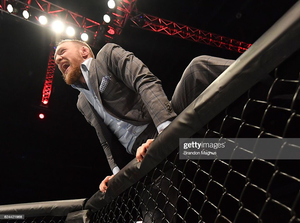 UFC lightweight and featherweight champion Conor McGregor climbs into the Octagon to celebrate with teammate Artem Lobov after his featherweight bout against Teruto Ishihara during the UFC Fight Night at the SSE Arena on November 19, 2016 in Belfast, Northern Ireland.
