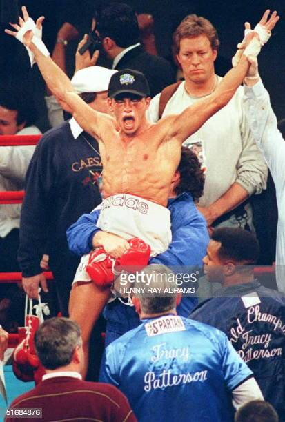 Lightweight Arturo Gatti raises his arms in victory and is lifted in the air after earning the International Boxing Federation lightweight title with...