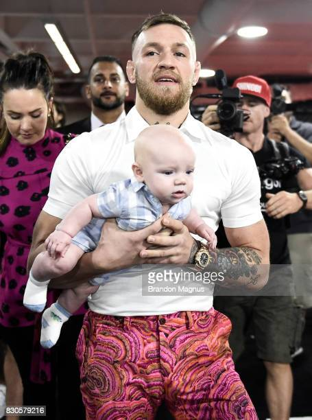 UFC lightweight champion Conor McGregor carries his son Conor McGregor Junior during a media workout at the UFC Performance Institute on August 11...