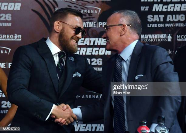 UFC lightweight champion Conor McGregor greets Nevada State Athletic Commission Executive Director Robert Bennett during a news conference at the KA...