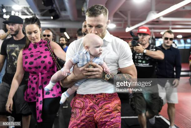 UFC lightweight champion Conor McGregor kisses his son Conor McGregor Junior during a media workout at the UFC Performance Institute on August 11...