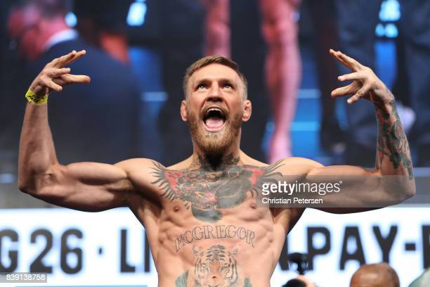 UFC lightweight champion Conor McGregor poses on the scale during his official weighin at TMobile Arena on August 25 2017 in Las Vegas Nevada...