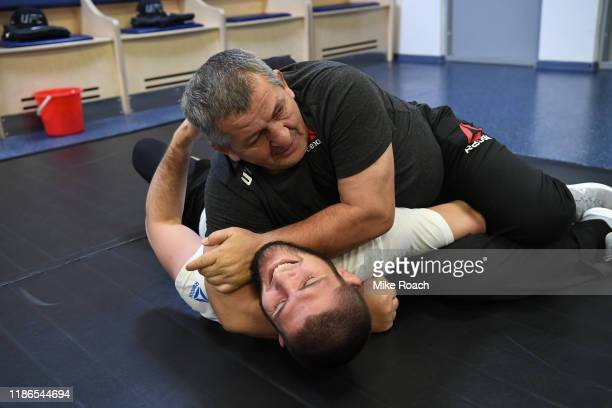 UFC lightweight champion Khabib Nurmagomedov grapples with his father Abdulmanap Nurmagomedov backstage during the UFC Fight Night event at CSKA...