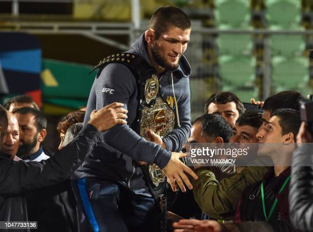 UFC lightweight champion Khabib Nurmagomedov of Russia carries his champions belt as he is escorted by fans upon the arrival in Makhachkala on...