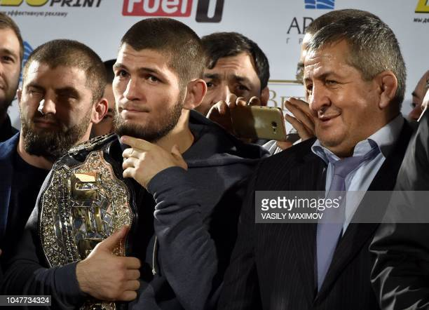 UFC lightweight champion Khabib Nurmagomedov of Russia holds his champions belt next to his father Abdulmanap during a ceremony upon the arrival at...