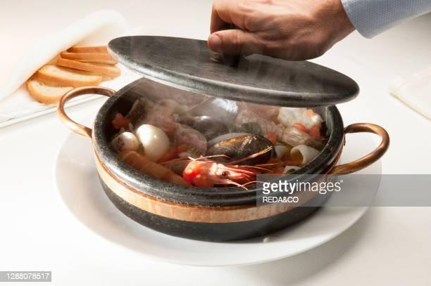 Ligurian sea fish soup in soapstone. Claudio Ristorante. Bergeggi. Liguria. Italy. Europe.