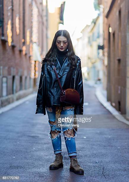 Lihan Guo is wearing a leather jacket bordeaux bag ripped denim jeans net tights boots during Milan Men's Fashion Week Fall/Winter 2017/18 on January...