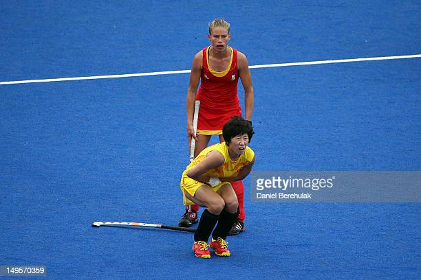 Lihua Gao of China grimaces in pain after AnneSophie Van Regemortel of Belgium strikes her with her stick during the Women's Hockey Match between...