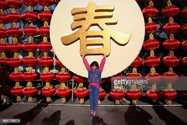 A liitle girl poses for photos as she and her family visit a temple fair to celebrate the Lunar New Year of Sheep during serious pollution on...