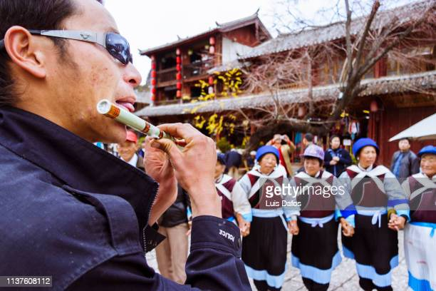 lijiang, traditional dancing and music - bamboo flute foto e immagini stock