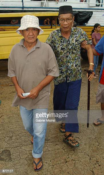 Lijo Castro a freed hostage who was held by Abu Sayyaf guerrillas for seven months walks to a ferry with a Muslim Imam June 29 2002 on the southern...