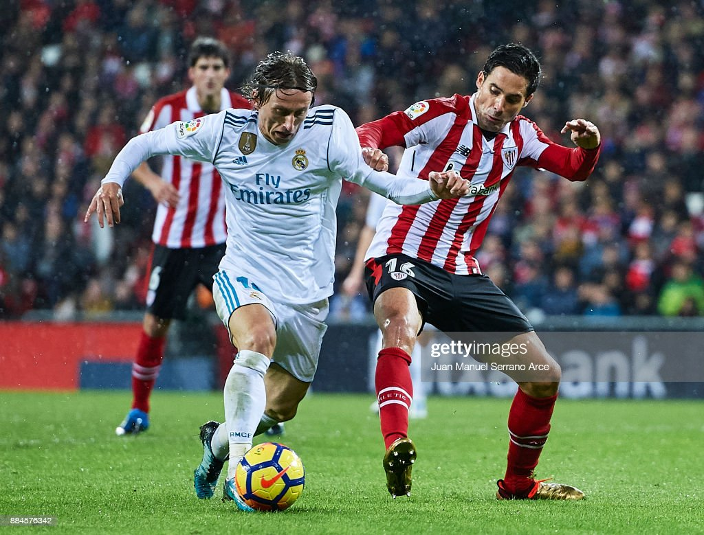 Lika Modric of Real Madrid CF (L) is challenged by Xavier Etxeita of Athletic Club (R) during the La Liga match between Athletic Club and Real Madrid at Estadio de San Mames on December 2, 2017 in Bilbao, Spain.