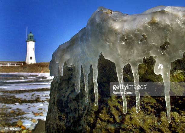 Like icing on a cake seawater spray formed icicles on the rocks of a breakwater protecting Scituate Harbor next to the Old Scituate Lighthouse The...