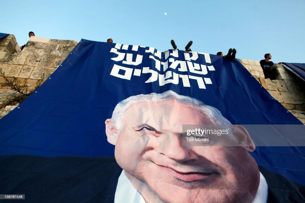 Likud party activists hang campaign posters of Israeli Prime Minister Benjamin Netanyahu that read in Hebrew ' Only Netanyahu will guard Jerusalem' under David's Citadel at Jaffa Gate in the Old city on January 20, 2013 in Jerusalem, Israel. The Israeli general election will be held on January 22.