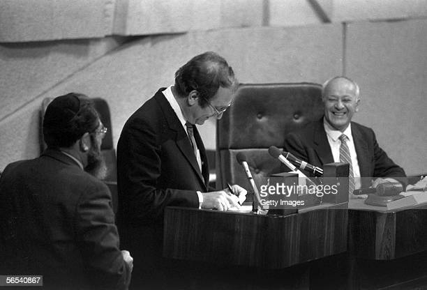 Likud party parliamentarian Ehud Olmert, center, signs his allegiance to the state as he is sworn in as Minister Without Portfolio in the Knesset,...