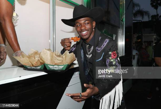 Lil Nas X enjoys Wingstop wings at the Old Town Road premiere party on May 17 2019 in West Hollywood California