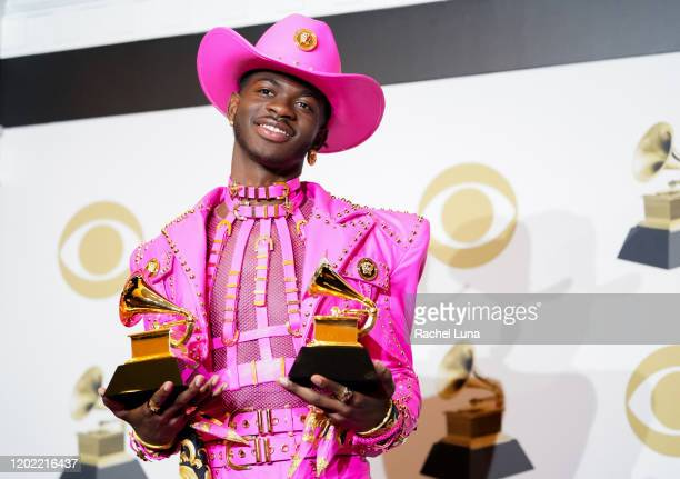 Lil Nas X poses in the press room with the awards for Best Music Video and Best Pop Duo/Group Performance during the 62nd Annual GRAMMY Awards at...