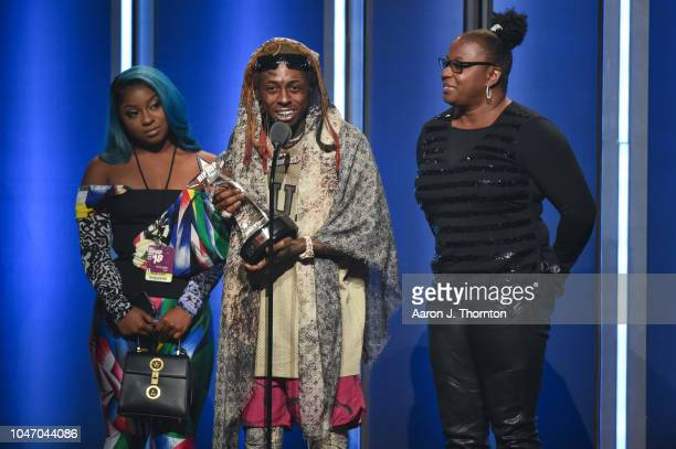 Lil Wayne speaks onstage while his Daughter Reginae Carter and Mother Jacida Carter stand beside him after receiving the 'I Am Hip Hop' award during...