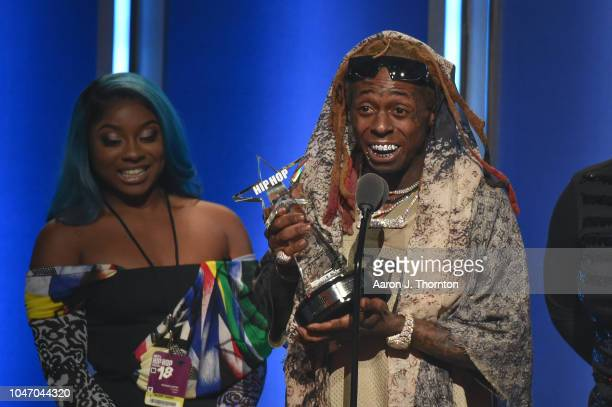 Lil Wayne speaks onstage with his Daughter Reginae Carter next to him after receiving the 'I Am Hip Hop' award during the 2018 BET Hip Hop Awards at...