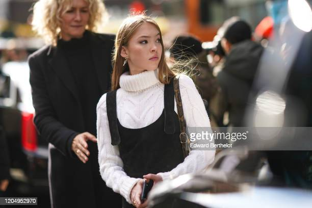 Lila Moss, daughter of Kate Moss, wears a white wool knitted turtleneck pullover, black overalls, outside Longchamp, during New York Fashion Week...