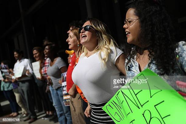 Lili Bach joins with other protesters against MiamiDade Mayor Carlos Gimenez's decision to abide by President Donald Trump's order that any...