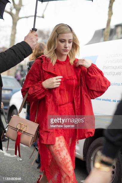 Lili Reinhart is seen on the street attending VALENTINO during Paris Fashion Week AW19 wearing VALENTINO red dress and boots with nude bag on March...