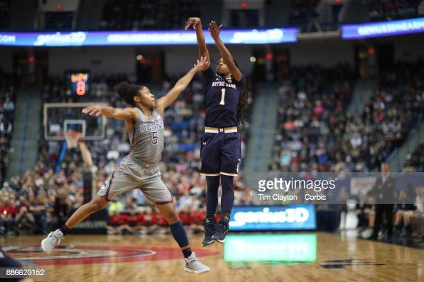 Lili Thompson of the Notre Dame Fighting Irish shoots while defended by Crystal Dangerfield of the Connecticut Huskies during the the UConn Huskies...
