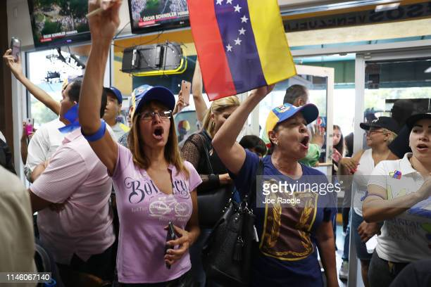 Lilian Martinez and Arelys Lopez join with others to show their support for the interim Venezuelan President Juan Guaido as they watch events unfold...