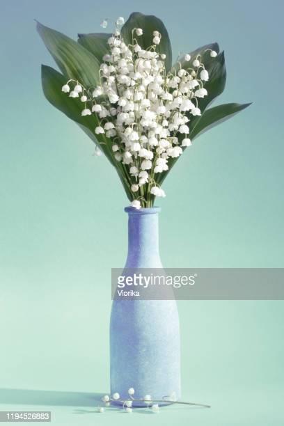 lirios del valle (convallaria majalis) - ramo de flores en un jarrón sobre un fondo de aguamarina - bouquet de muguet fotografías e imágenes de stock