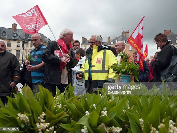 Lilies of the valley lay on the ground as people take part in a May Day rally on May 1 2014 in Rennes western France AFP PHOTO / DAMIEN MEYER
