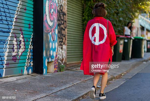 Liliy Zhang wearing a long red light jacket with a peace print from You Planet a black Chanel bag and black Stella McCartney platform creeper as...
