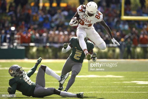 Lil'Jordan Humphrey of the Texas Longhorns leaps past defenders Jameson Houston and Taion Sells of the Baylor Bears in the second half at McLane...